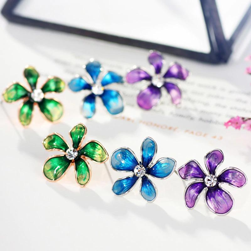 Asymmetrical flower earrings available in bright shades of blue, green, and purple.