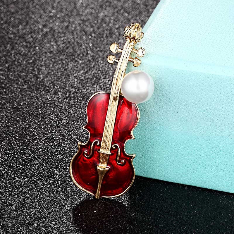 Violin Virtuoso Brooch - A red and gold coloured enamel brooch shaped like a violin, adorned with a large pearl.
