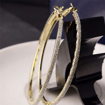 The Mariah Hoop Earrings - A pair of large 6cm hoop earrings encrusted with crushed rhinestone glitter, available in yellow gold or silver tone.