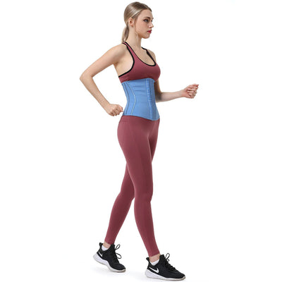 Artemis Vented Fitness Waist Trainer - This picture shows an athletic young woman wearing sportswear, and the waist trainer over top. The waist trainer has structured curved boning around the waist, and is made of vented latex. It is a cute baby blue colour.