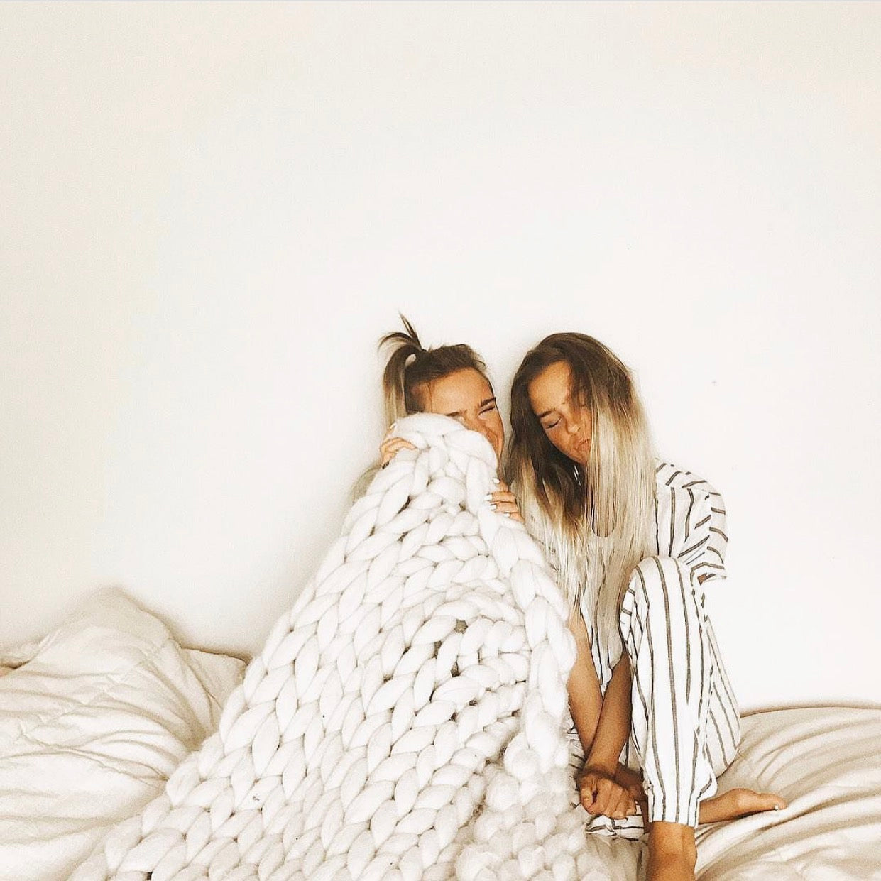 Two Girls Cuddle with Chunky Knit Blanket