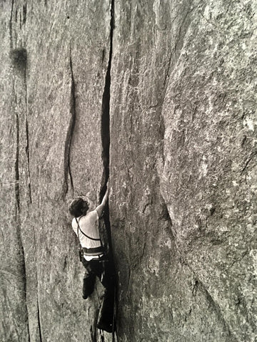 Crack Climbing in the 70s with Jim Bridwell. A man reaches deep into a vertical crack in Yosemite as he attempts to ascend Cookie  Cliff