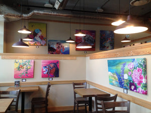 cafe with chairs, tables, and paintings on wall