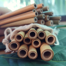 Load image into Gallery viewer, Multiple Bamboo straws of the brand Sipeco resting on each other on a bed of leaves the straws are made from natural bamboo