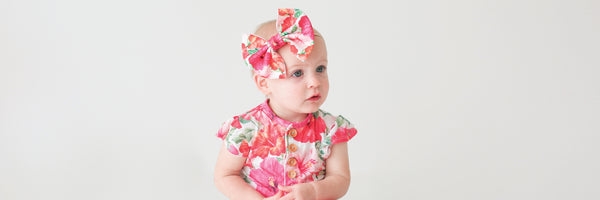 baby girl wearing floral romper with bow