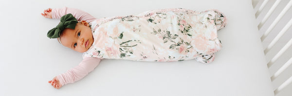 baby wearing floral infant sleeping bag in crib
