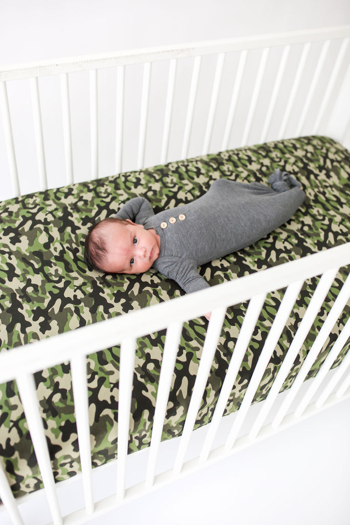 baby laying on camo print crib sheet cover
