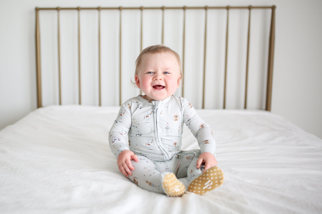 baby boy wearing zipper pajamas on bed