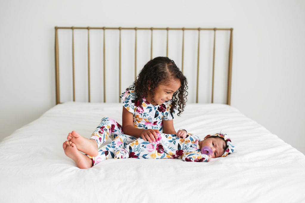 baby in newborn knotted gown, sister in matching floral print