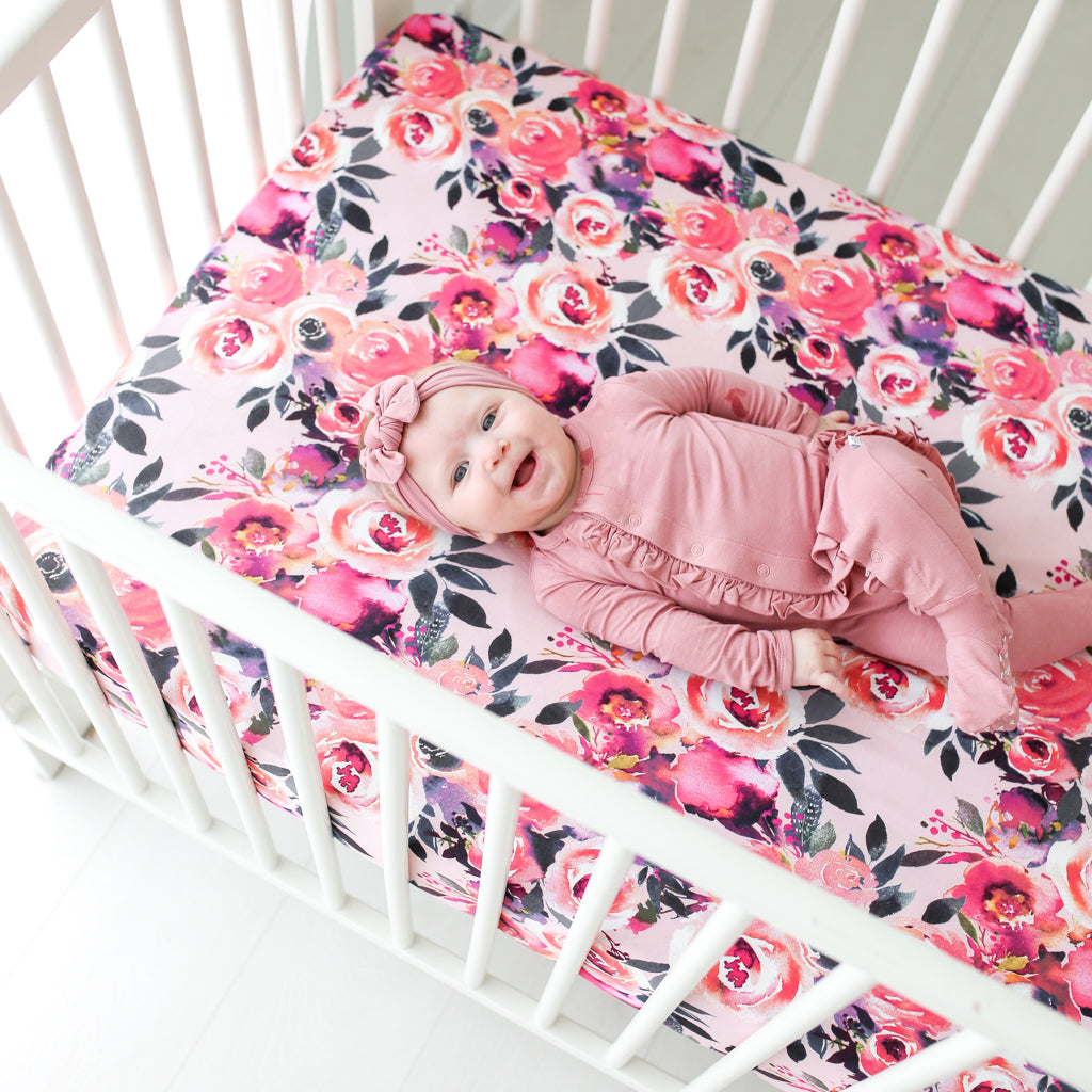 baby girl laying on floral baby crib sheets