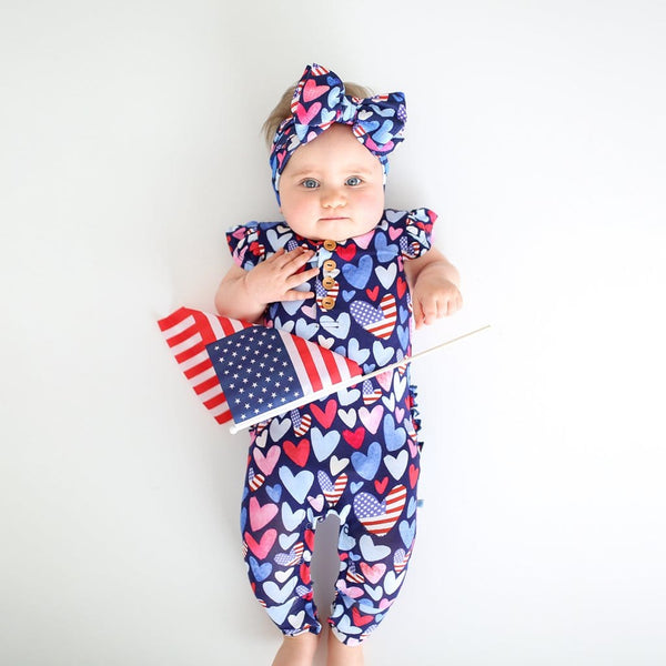 Baby lying down wearing Liberty ruffled cap sleeve henley romper