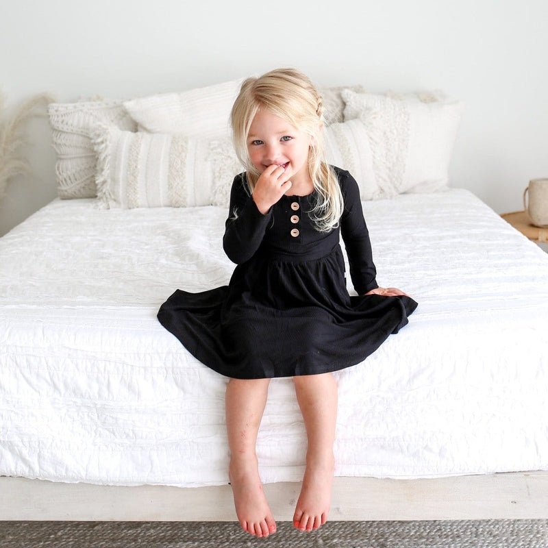 Toddler on bed wearing Black Ribbed Long Sleeve Twirl Dress