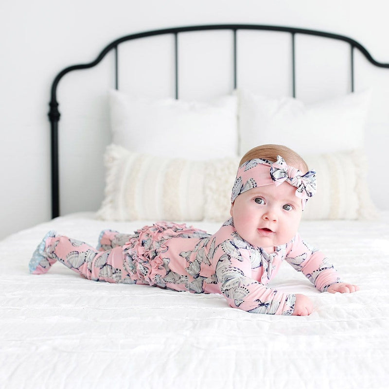 Baby on bed wearing Beatrice Footie Ruffled Zippered One Piece with butterfly pattern