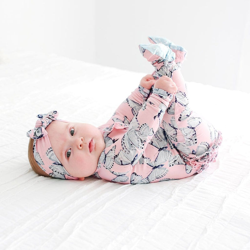 Baby lying on bed wearing Beatrice Footie Ruffled Zippered One Piece with butterfly pattern