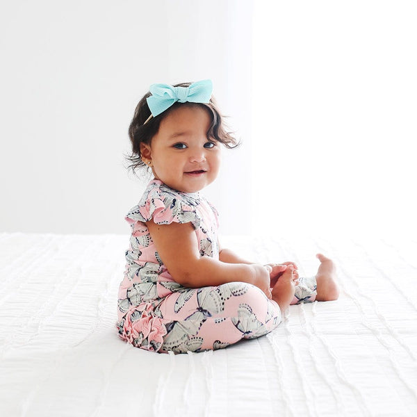 Baby sitting wearing Beatrice Ruffled Cap Sleeve Romper with butterfly pattern