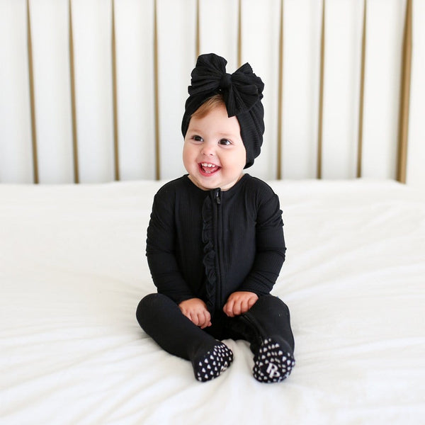 Baby on bed wearing Black Ribbed Footie Ruffled Zippered One Piece