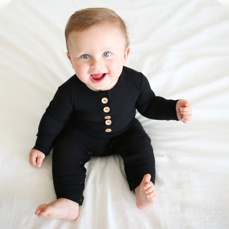 Baby wearing Black Ribbed Long Sleeve Henley Romper