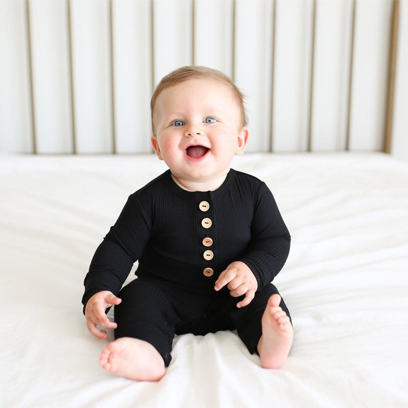 Sitting baby wearing Black Ribbed Long Sleeve Henley Romper