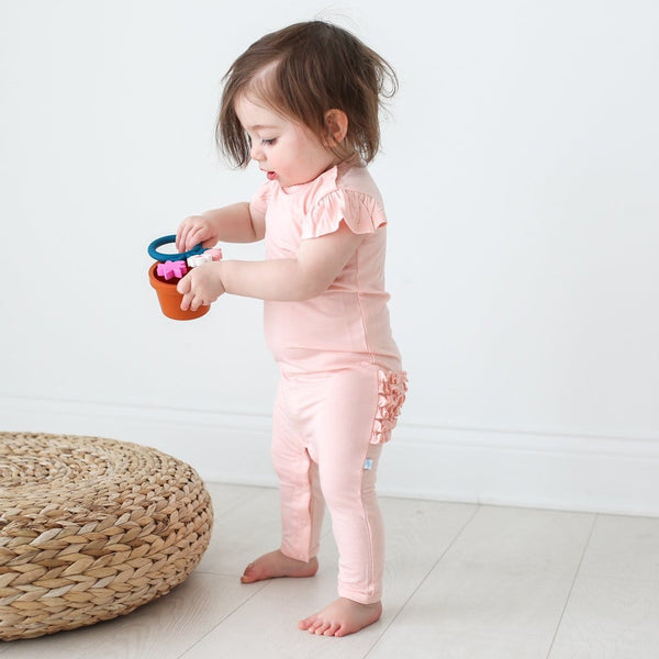 Baby wearing blush ruffled cap sleeve romper