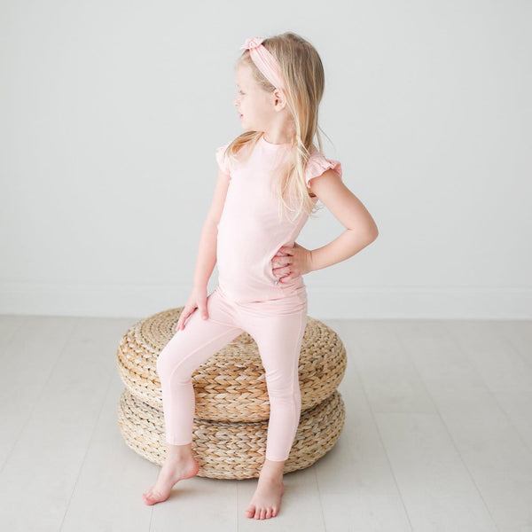 Toddler wearing blush ruffled cap sleeve pajamas