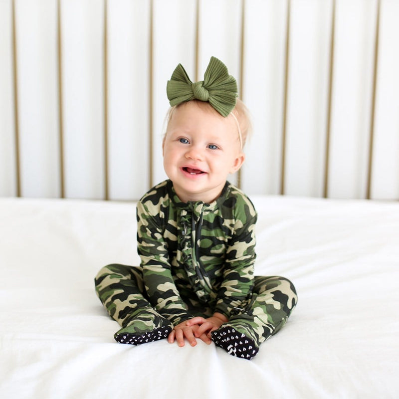 Baby on bed wearing Cadet Footie Ruffled Zippered One Piece