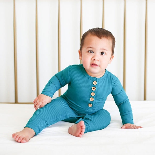 Baby sitting wearing Cerulean Ribbed Long Sleeve Henley Romper