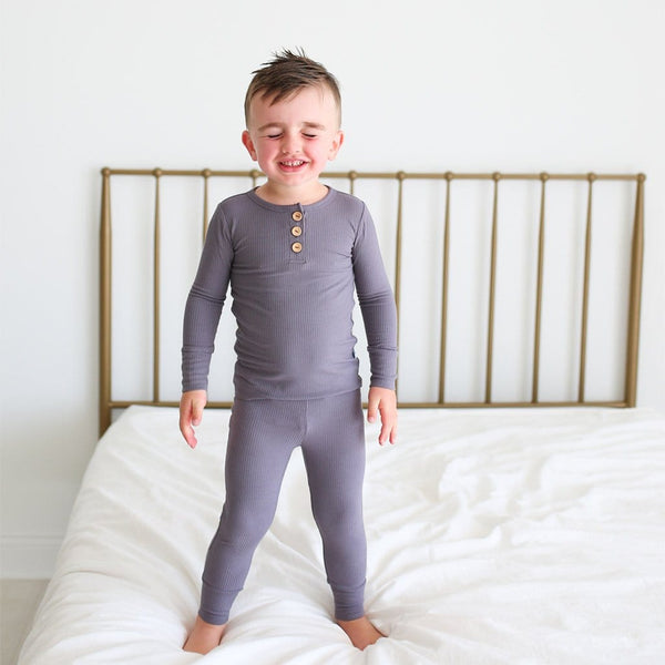 Toddler on bed wearing Charcoal Ribbed Long Sleeve Henley Pajamas