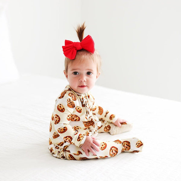 Sitting baby on Chip Footie Ruffled Zippered One Piece with cookie pattern