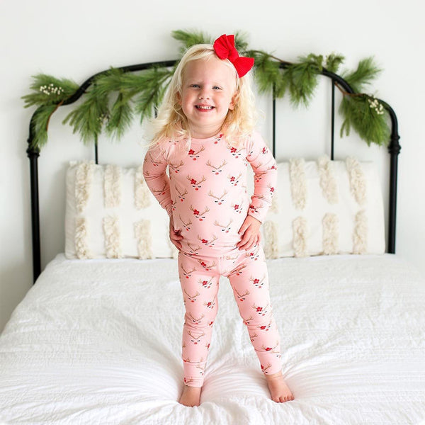 Toddler on bed wearing Clarice Long Sleeve Pajamas with Reindeer Print