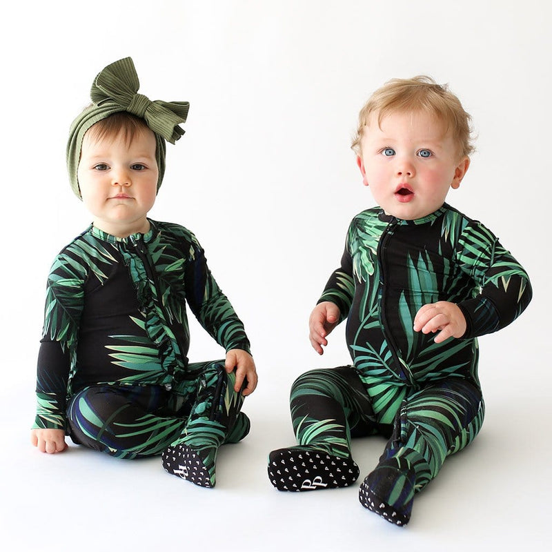 Baby sitting wearing Cooper Footie Zippered One Piece with leaf design