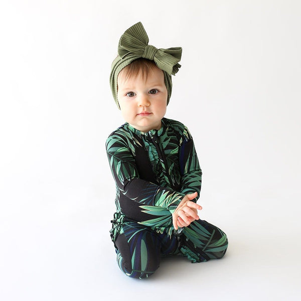Baby sitting wearing Cooper Footie Ruffled Zippered One Piece with leaf design