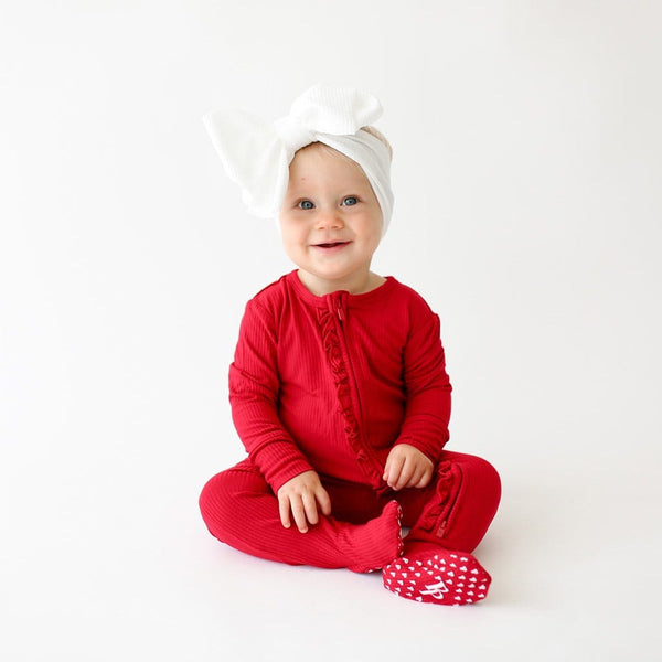 Baby on white headband wearing Crimson Ribbed Footie Ruffled Zippered One Piece