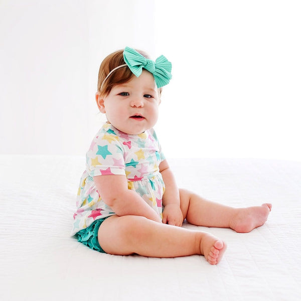 Sitting baby wearing Crissy Short Sleeve Peplum Ruffled Bummie Set with star pattern