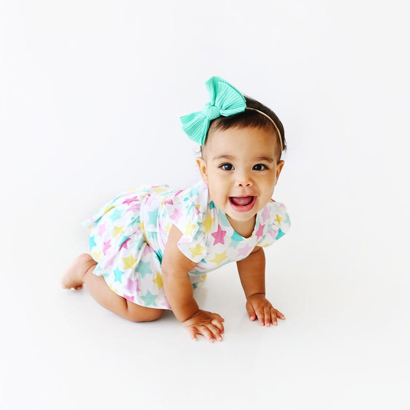 Crawling baby wearing Crissy Ruffled Cap Sleeve Twirl Skirt Bodysuit with star pattern