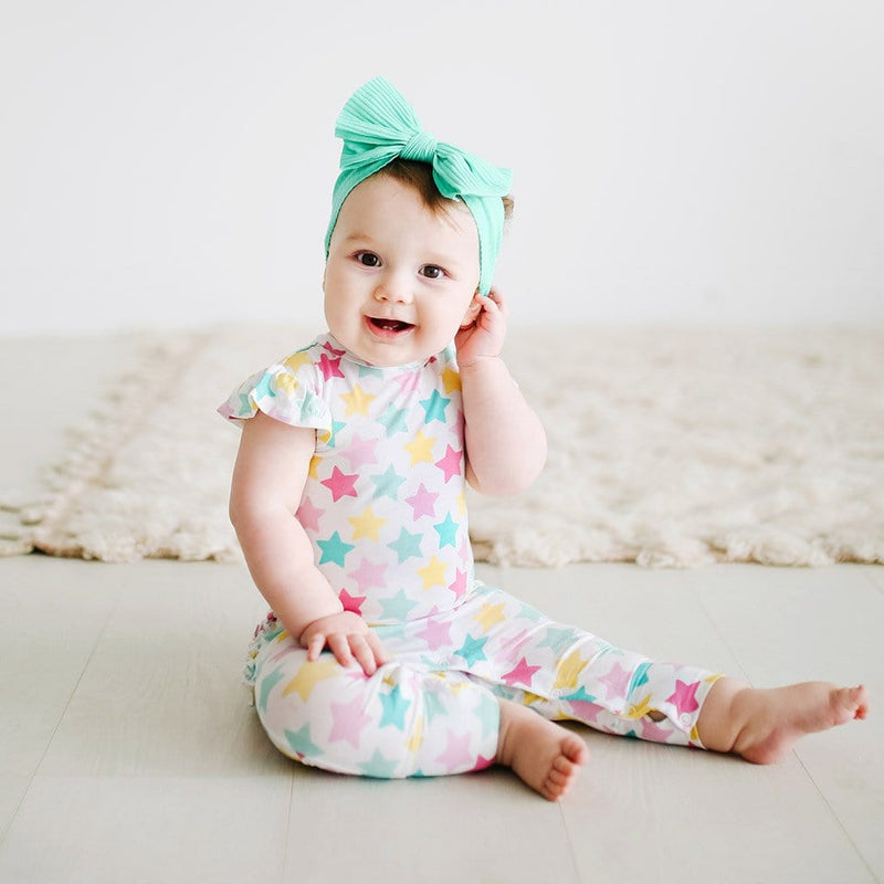 Sitting baby wearing Crissy Ruffled Cap Sleeve Romper with star pattern