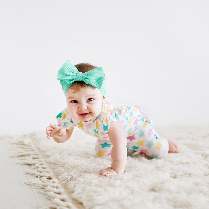 Crawling baby wearing Crissy Ruffled Cap Sleeve Romper with star pattern