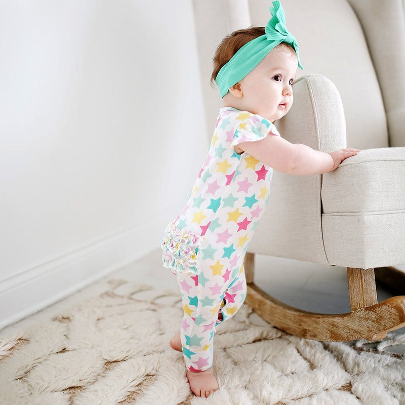 Baby standing by a chair wearing Crissy Ruffled Cap Sleeve Romper with star pattern