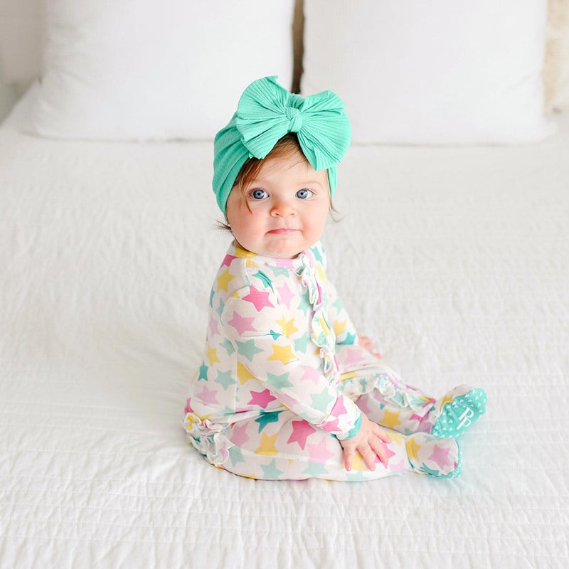 Baby on bed wearing Crissy Footie Ruffled Zippered One Piece with star pattern