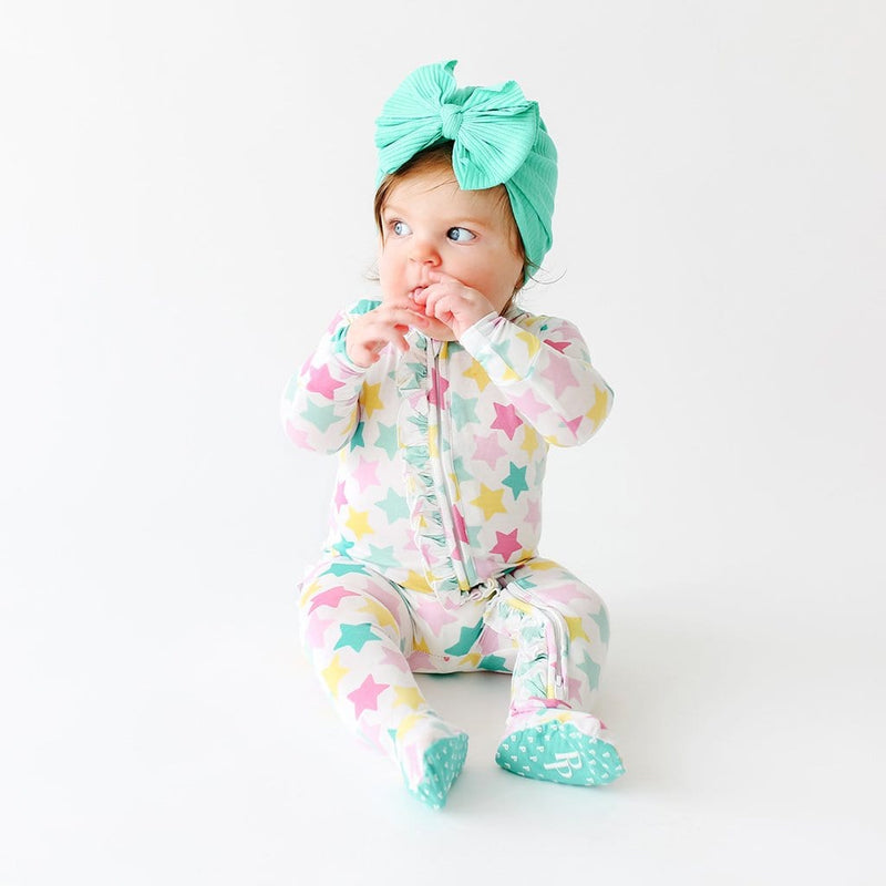 Baby wearing Crissy Footie Ruffled Zippered One Piece with star pattern