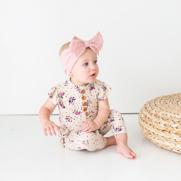 Sitting baby wearing Frances ruffled cap sleeve romper
