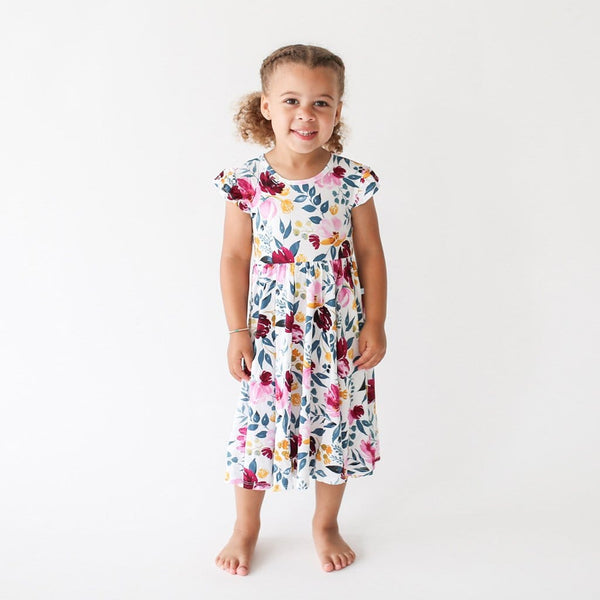 Baby standing wearing Jozie twirl dress