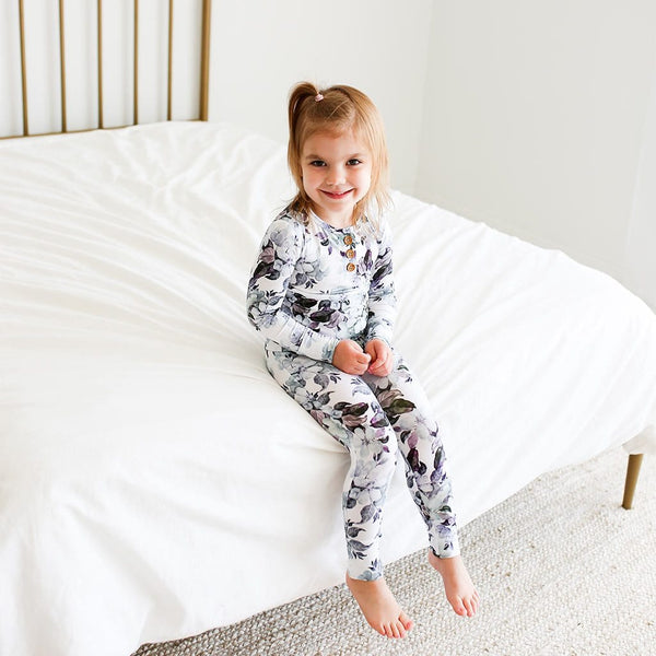 Baby sitting on bed wearing Jules Floral Long Sleeve Henley Pajamas