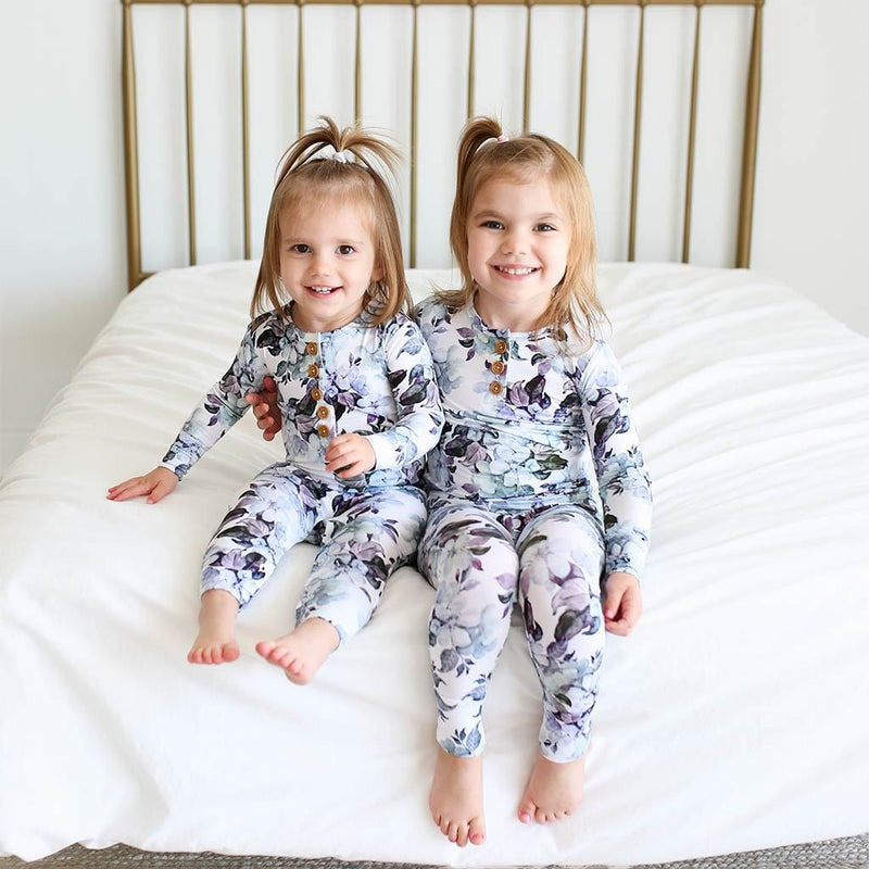 Sisters sitting on bed wearing Jules Floral Long Sleeve Ruffled Henley Romper