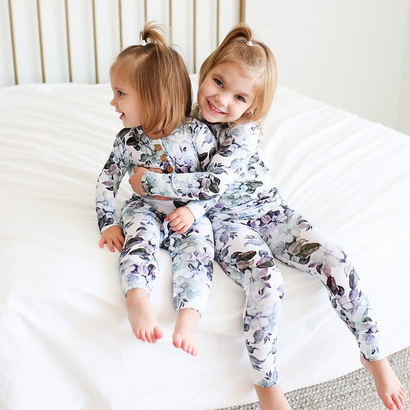 Kid hugging sister wearing Jules Floral Long Sleeve Henley Pajamas