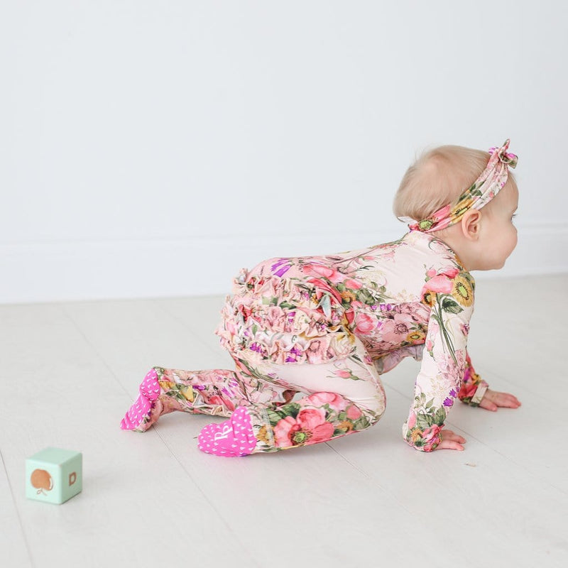 Baby crawling wearing June footie ruffled snap one piece