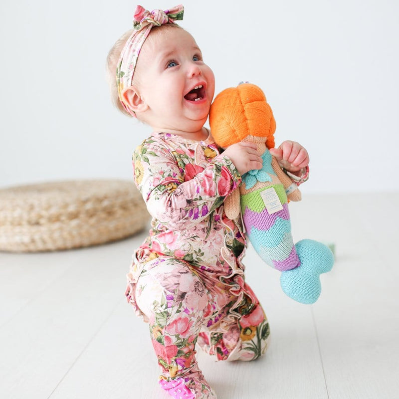 Baby playing wearing June footie ruffled snap one piece