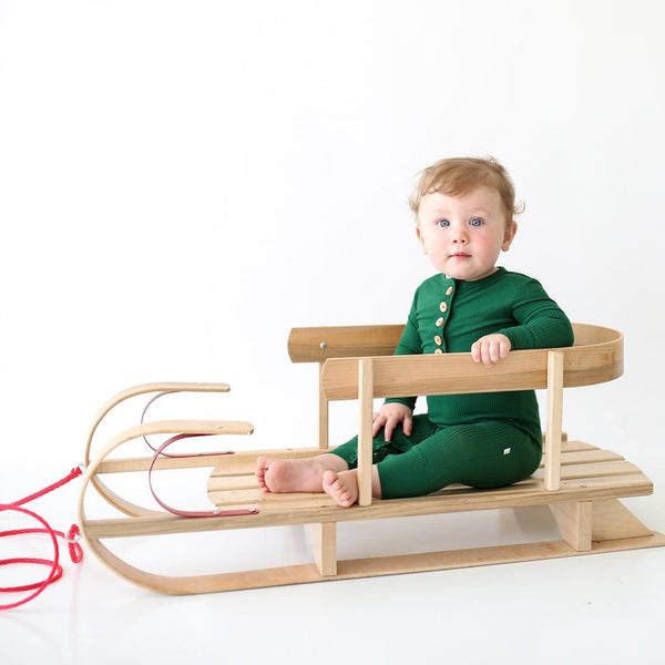 Baby on sled wearing Juniper Green Ribbed Long Sleeve Henley Romper