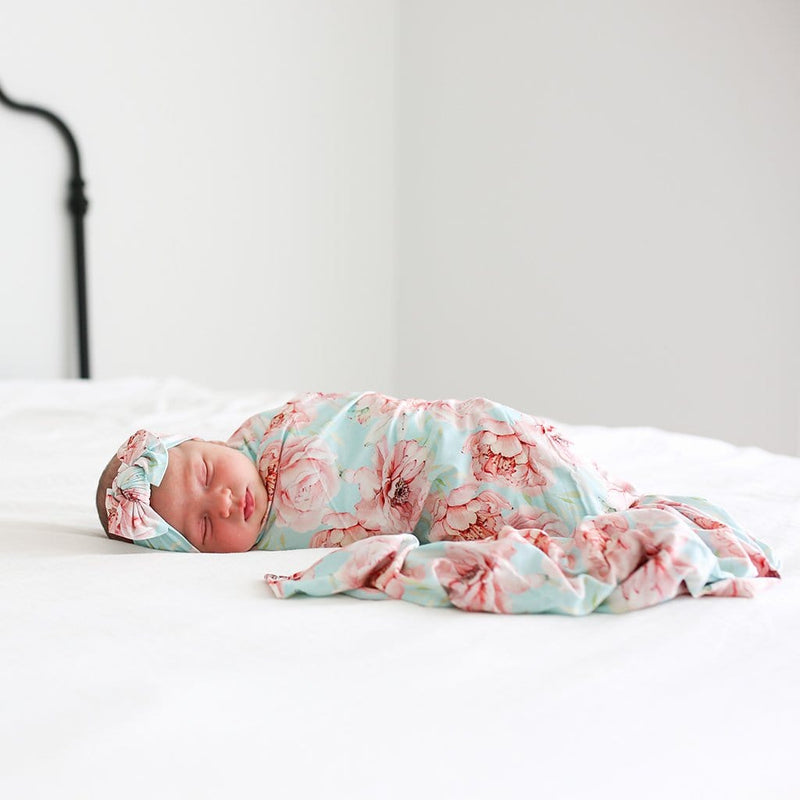 Baby lying on bed wearing Kennedy Swaddle Headband Set