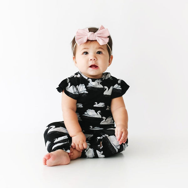 Baby wearing Leia Ruffled Cap Sleeve Romper with swan pattern