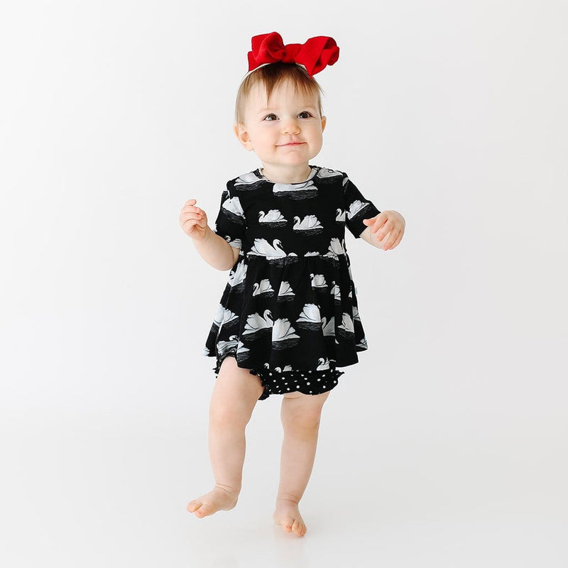 Baby wearing Leia Short Sleeve Peplum Ruffled Bummie Set with swan pattern